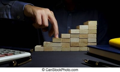 Career path. Stairs from wooden blocks and fingers that...
