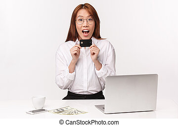 Career, work and women entrepreneurs concept. Close-up portrait cheerful young asian woman sitting in office with laptop, money, hold credit card, look amused, got first paycheck