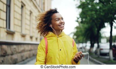 Carefree African American student is walking, listening to...