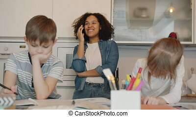 Carefree Afro-American lady nanny chatting on mobile phone while children doing homework studying