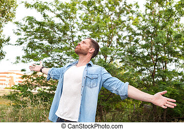 Carefree and free man raising his arms