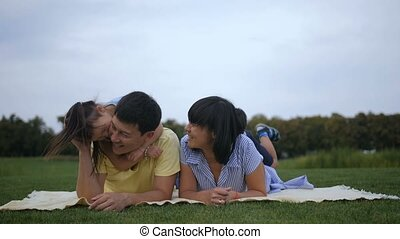 Carefree asian children piled up on top of parents -...