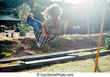 Carefree barefoot girl on swing in sun light - Back view of...