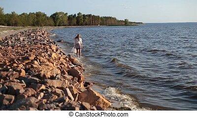 Carefree beautiful woman strolling seashore