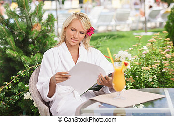 Carefree beauty. Attractive young women in bathrobe reading the magazine while sitting at the table with a cocktail on it