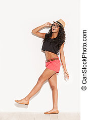Carefree beauty. Full length side view of beautiful young African woman in funky wear adjusting her glasses and smiling while posing against white background