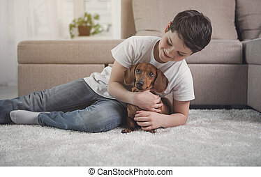 Carefree boy hugging his dog with love