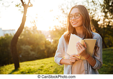 Carefree brunette woman in eyeglasses holding book and looking away