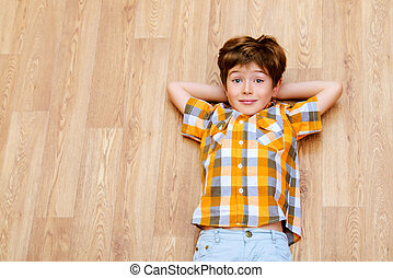 carefree child - Happy smiling boy lying on a floor at home...