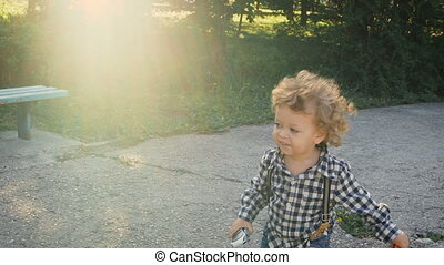 Carefree childhood. Cute curly little boy running on the track. He is holding a toy car.