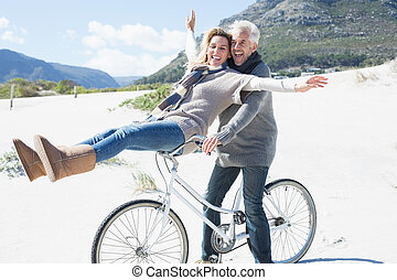 Carefree couple going on a bike ride on the beach on a ...