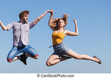 Carefree couple jumping against blue sky