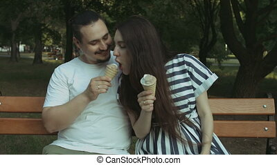 Carefree couple with ice cream resting on bench