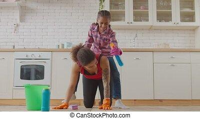 Carefree daughter piggybacking mom during cleaning - ...