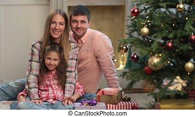 Carefree family of three waving hands at Christmas