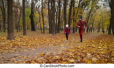 Carefree father and daughter running in autumn park -...