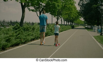Carefree father and little daughter riding scooters