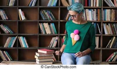 Carefree female student using phone in library