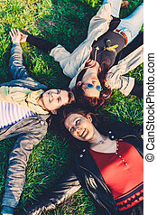 Carefree friends - Three happy friends relax on the green...