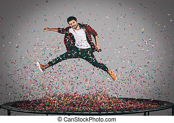 Carefree fun. Mid-air shot of handsome young man jumping on...