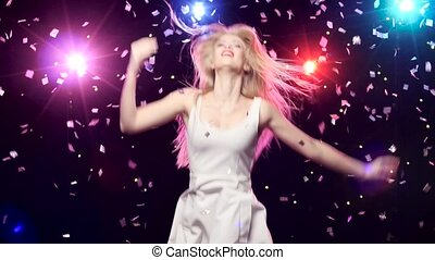 Carefree girl are dancing against disco lights and glitter confetti