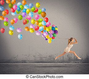 Carefree and happy girl jumping with balloons