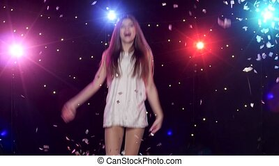 Carefree girl dancing and throws glitter confetti against disco lights