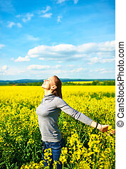Carefree girl - Girl with outstretched arms at colza field