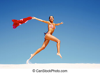 Carefree girl - Image of happy girl running down sandy beach...