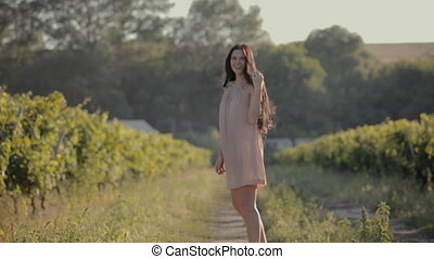 Carefree girl walking along the vineyards