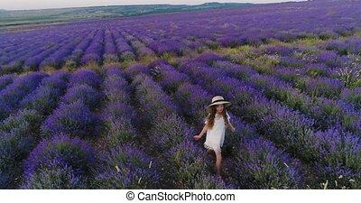 Carefree girl walks in the fragrant fields of lavender....