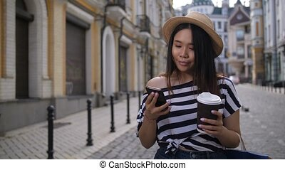Carefree girl with cellphone walking along street