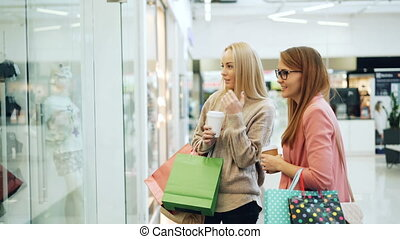 Carefree girls are chatting in shopping center pointing at...