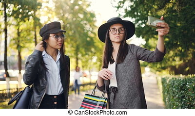 Carefree girls are taking selfie using smartphone posing with shopping bags in the street wearing stylish clothes. Modern technology, consumerism and fun concept.