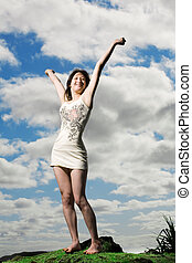 Carefree - Happy girl raises arms above head with sky in...