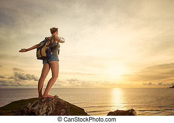 Carefree happy woman traveler with backpack enjoying sunset view