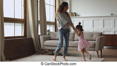 Carefree happy young mother lifting joyful small kid daughter.