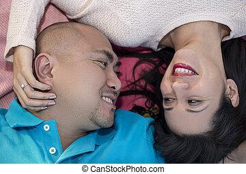 Carefree Hispanic Couple - Engaged latino couple laying on a...