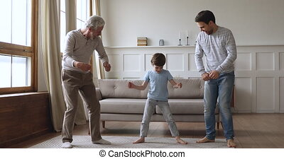 Carefree intergenerational men family dance together in living room