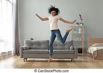 Carefree joyful african girl jumping dancing alone at home