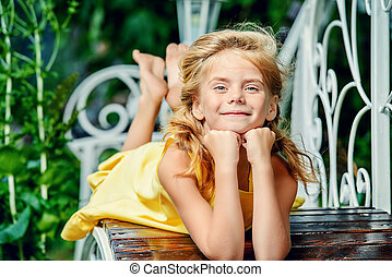 carefree kid - Happy smiling girl resting in a beautiful ...