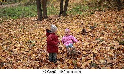 Carefree kids playing in a pile of fall leaves