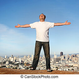 Carefree living - A man standing on a hill with a view of...