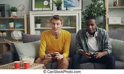 Carefree male students are playing video game on couch at home, pressing buttons on joystick concentrated on activity. Friendship and modern technology concept.