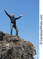 Carefree man - A man standing on a cliff with his arms ...