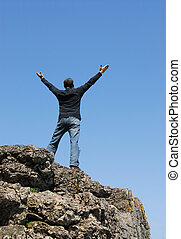 Carefree man - A man standing on a cliff with his arms...