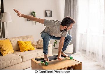 Carefree man skateboarding on coffee table