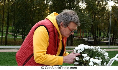 Carefree mature adult man in bright clothing with pleasure sniffing fragrant flowers in the park. Close-up. Outdoors.