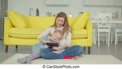 Carefree mom and girl playing online with tablet pc -...
