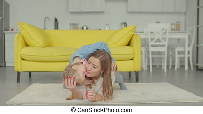 Carefree mother and daughter relaxing on the floor